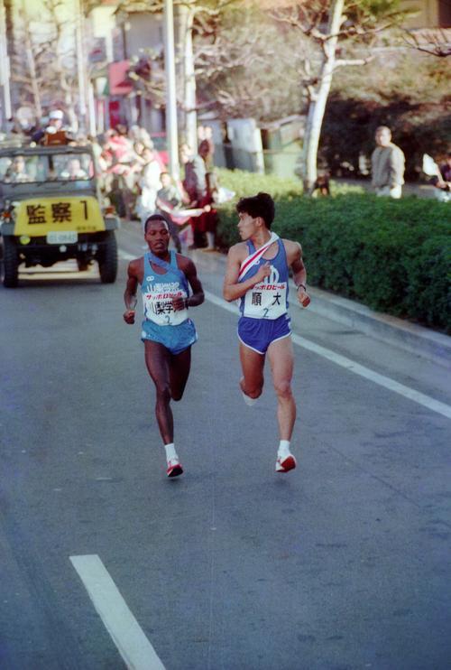 往路2区 1位順天堂大に48秒差の8位でタスキをもらった山梨学院大オツオリ(左=1年、区間1位)は、6.2キロで順天堂大・鈴木賢一(右=3年、区間3位)をとらえ、7人抜きでトップに躍り出る鮮烈デビュー=1989年1月2日