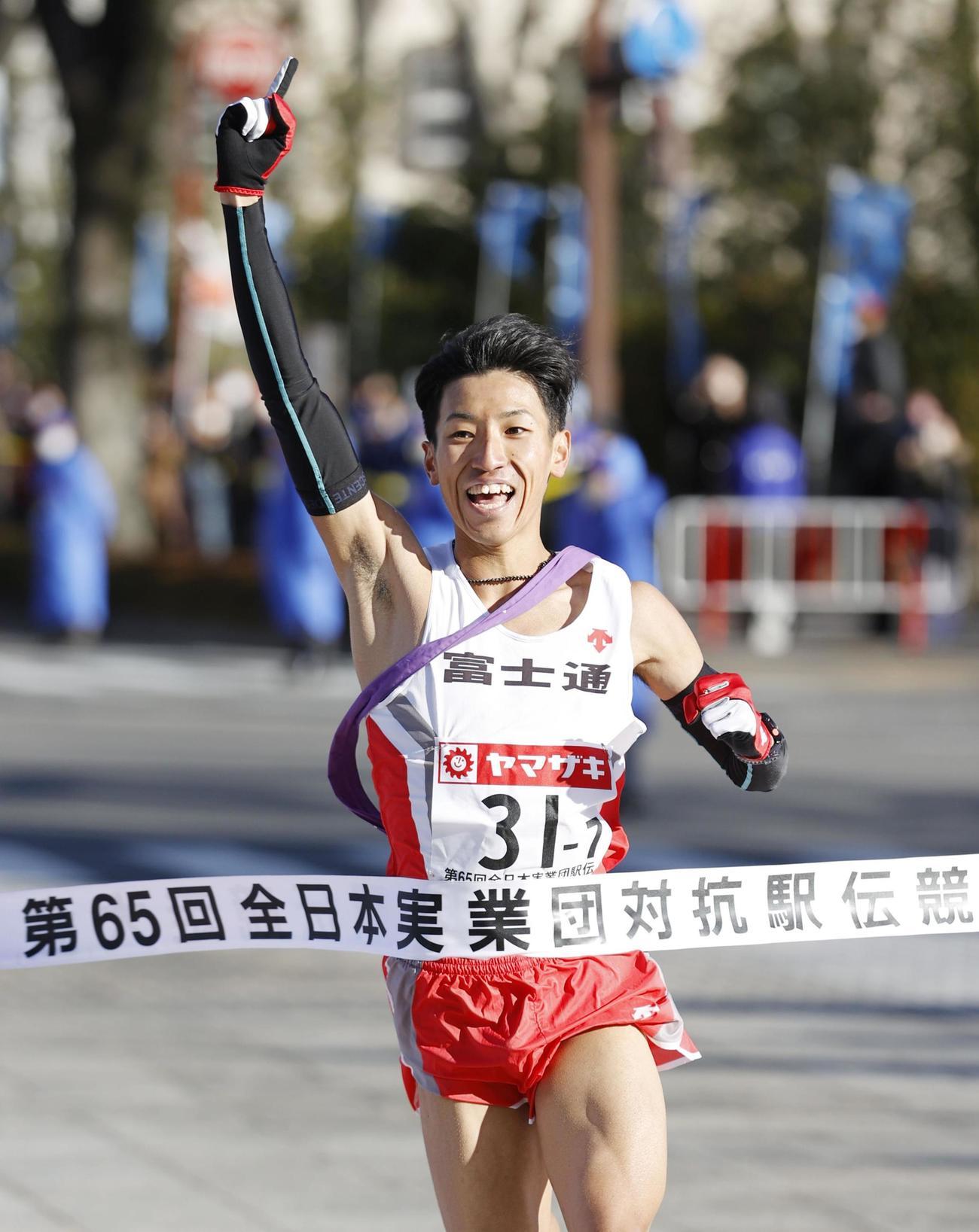 12年ぶり3度目の優勝を決め、指を突き上げる富士通のアンカー・浦野雄平(共同)