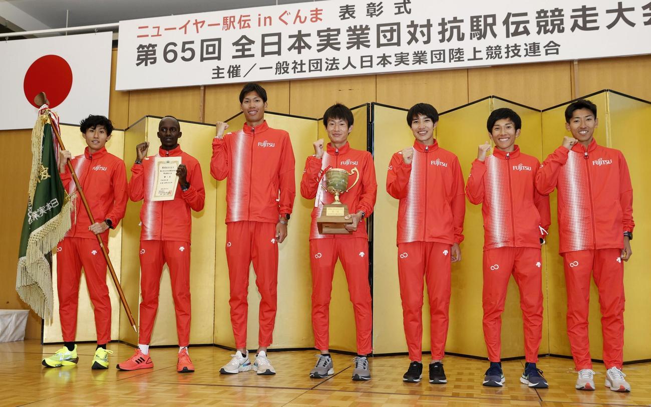 優勝し、表彰式で笑顔を見せる中村匠吾(中央)ら富士通の選手たち(共同)