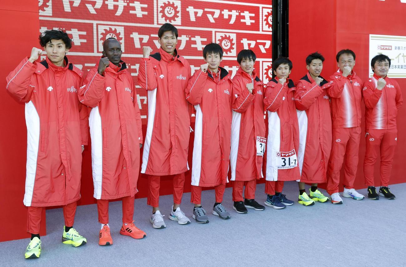 優勝し、笑顔でポーズをとる中村匠吾(左から4人目)ら富士通の選手たち(共同)
