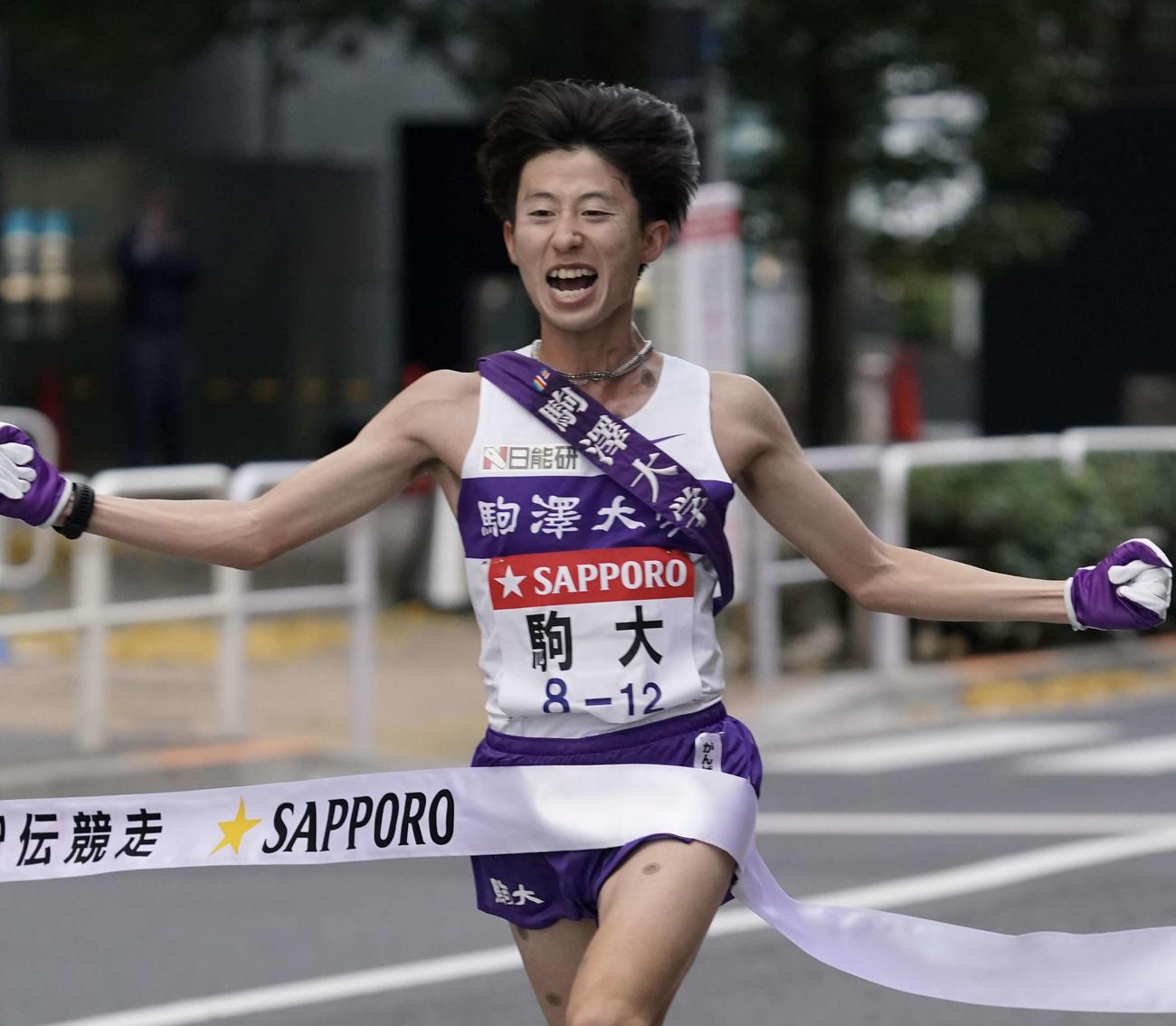 総合優勝し、ゴールテープを切る駒大10区石川(撮影・菅敏)