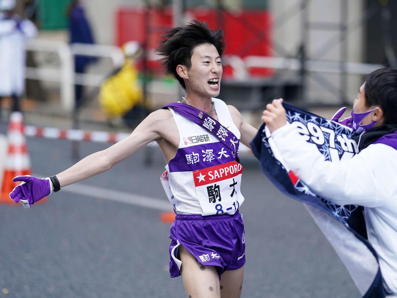 逆転優勝しチームメートに迎えられる駒大10区石川(左)(撮影・江口和貴)