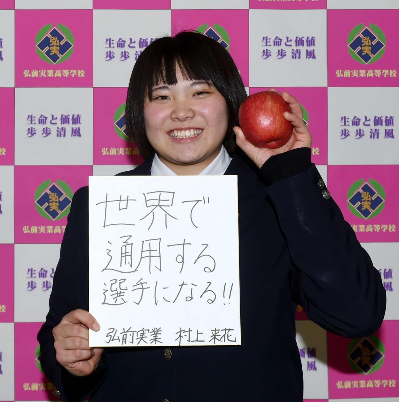 今年の目標を記した色紙と青森県名産のりんご持ちながら笑顔を見せる弘前実・村上(撮影・相沢孔志)
