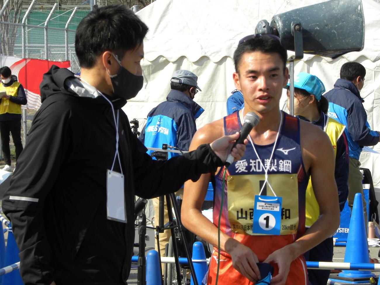 陸上の日本選手権男子20キロ競歩を制し、インタビューを受ける山西利和(右)(撮影・松本航)