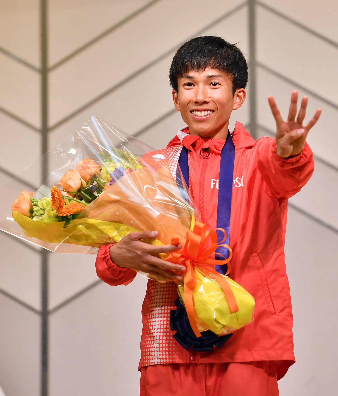 2時間4分56秒の日本人初の4分台で優勝した鈴木はアワードセレモニーに参加し4のポーズで笑顔を見せる(撮影・上田博志)