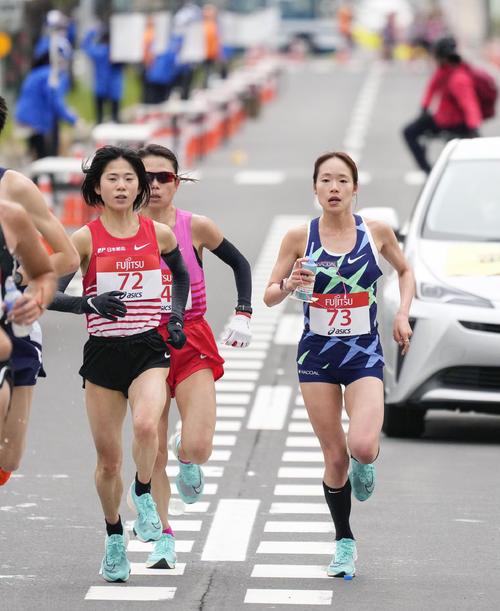 女子ハーフマラソン レース中盤で、ドリンクを手に力走する一山麻緒(右)。左手前は鈴木亜由子(共同)