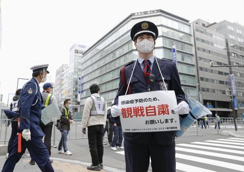 札幌市で開催される東京五輪マラソンのテスト大会で、観戦自粛を呼び掛ける案内を掲げる警備員(共同)