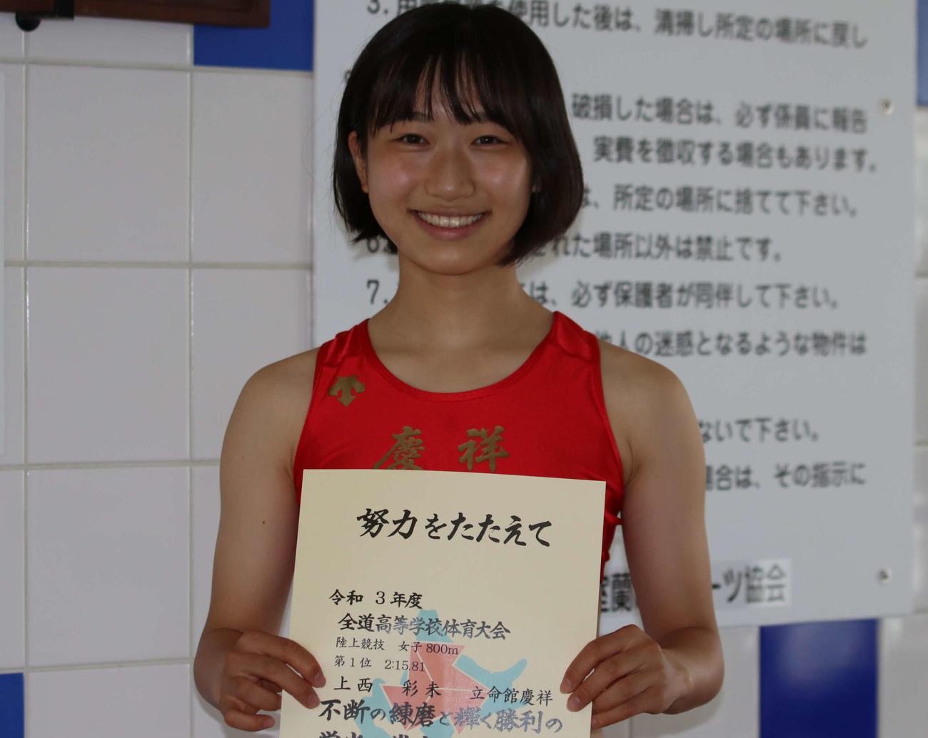 女子800メートルで優勝を決め、賞状を手に笑顔をみせる立命館慶祥の上西(撮影・山崎純一)