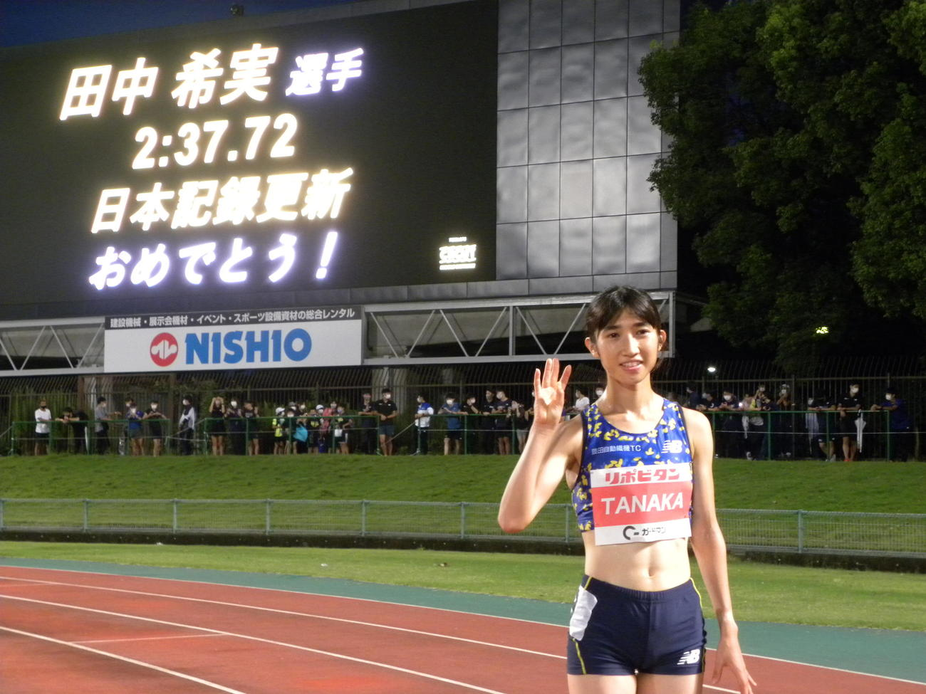 女子1000メートルの日本新記録を樹立し、3本の指を立てて3種目目の達成を表現する田中(撮影・松本航)