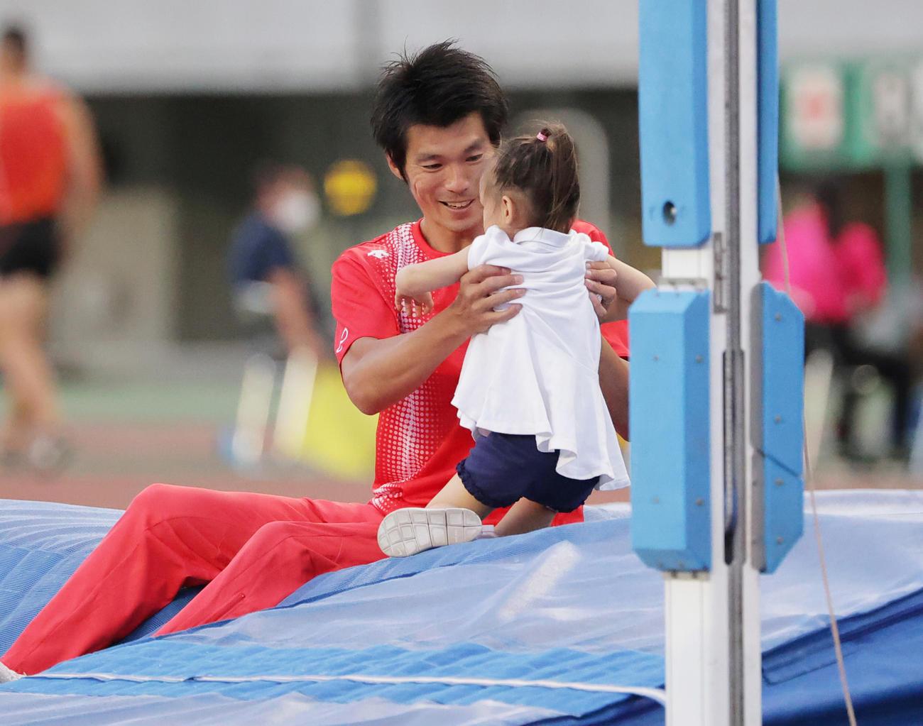 男子走り棒高跳び 現役最後の競技を終えマットの上で娘と記念撮影を行う沢野大地(撮影・清水貴仁)