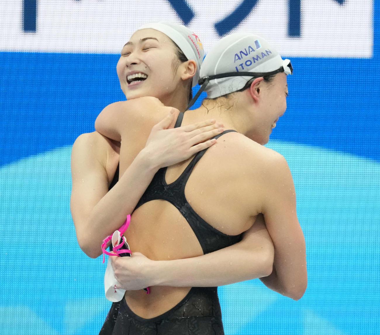 女子100メートル自由形で優勝した池江(左)は4位の大本と抱き合って喜ぶ