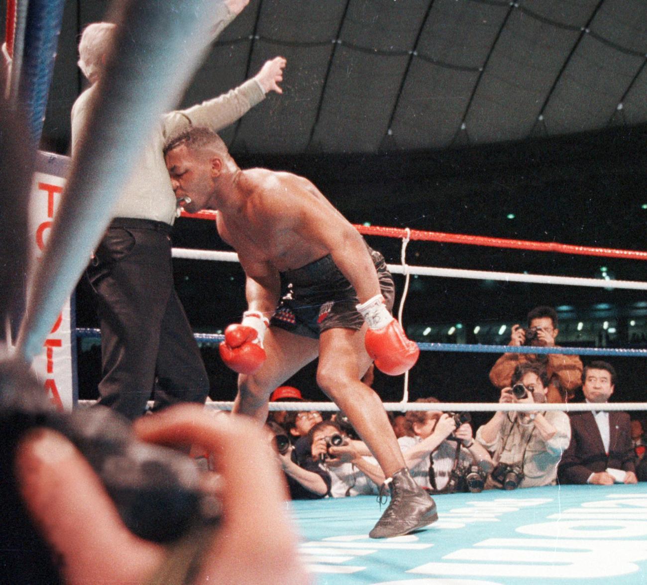 WBA・IBF・WBC世界ヘビー級タイトルマッチ 10回、ダグラスからダウンを奪われKO負けしたマイク・タイソンはダメージからレフェリー(左)に寄りかかる(1990年2月11日撮影)
