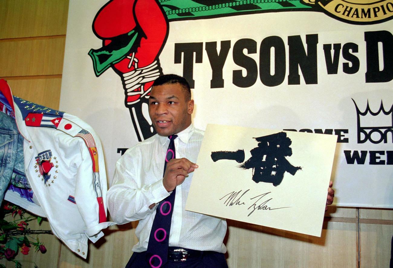 ダグラスとの統一ヘビー級タイトルマッチのため来日し、会見で「一番」と自らのサインが書かれたボードを見せるマイク・タイソン(1990年1月16日)