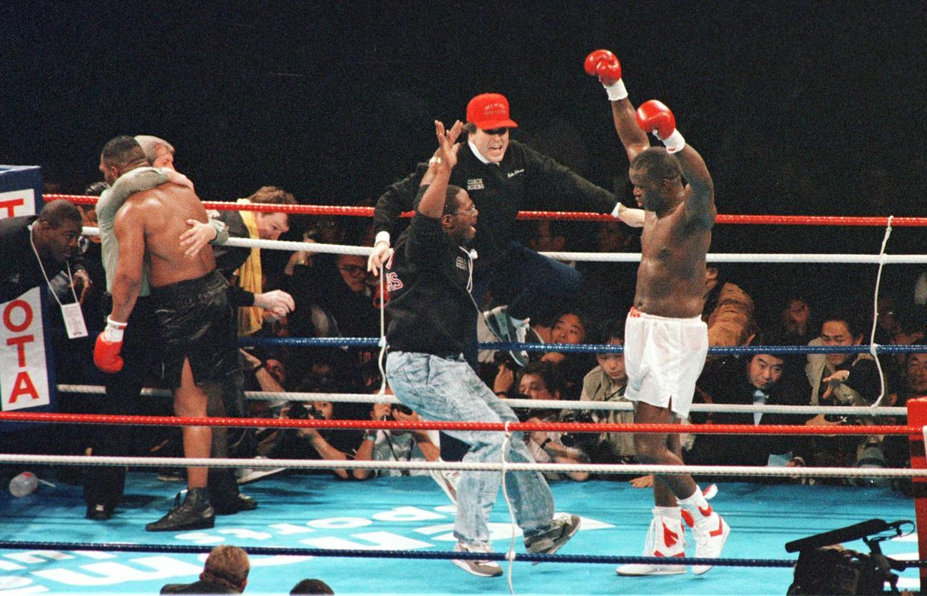 KO勝ちし両手を突き上げ喜ぶジェームス・ダグラス(右)。左から2人目はKO負けを喫しレフェリーに抱えられるマイク・タイソン(1990年2月11日)