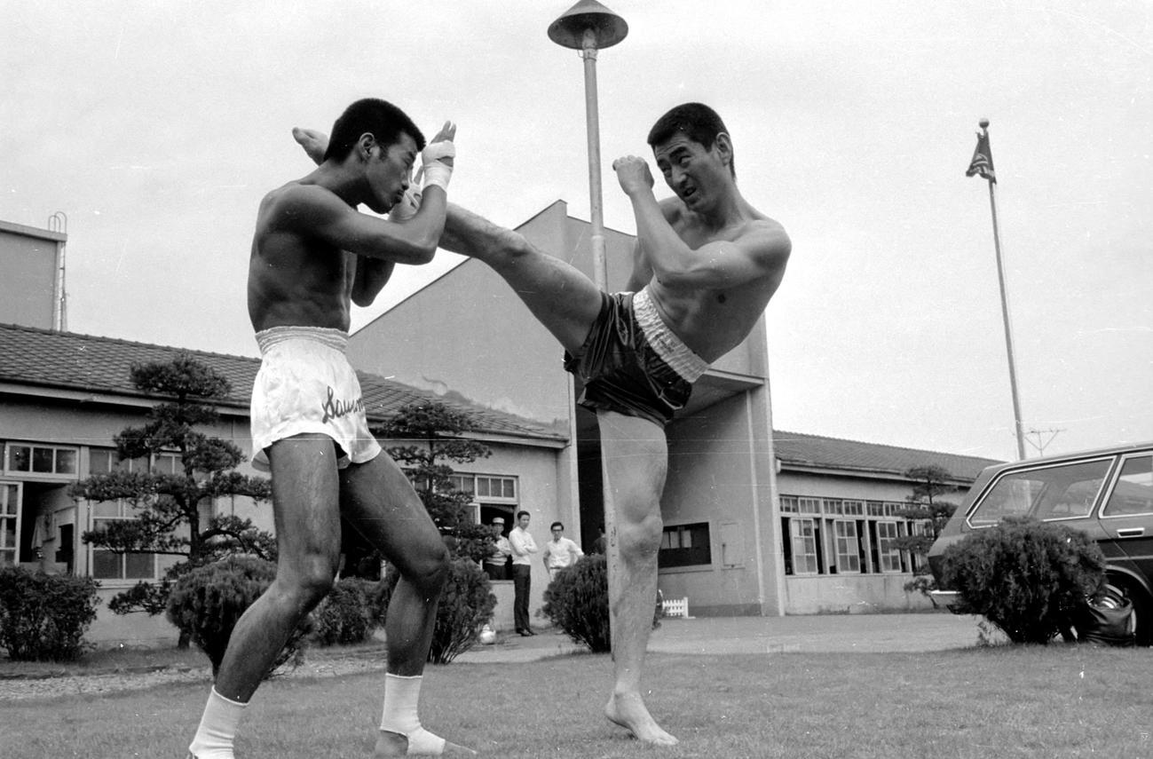 キックボクサー沢村忠(左)の指導でキックボクシングの訓練を受ける高倉健(1968年9月撮影)