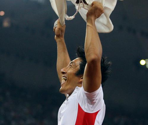 北京五輪陸上男子400mリレーで銅メダルを獲得し、日の丸を振って喜ぶ朝原宣治。
