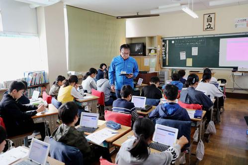 プログラミングの授業を受ける浅羽北小の児童たちと佐藤規之教諭(中央)