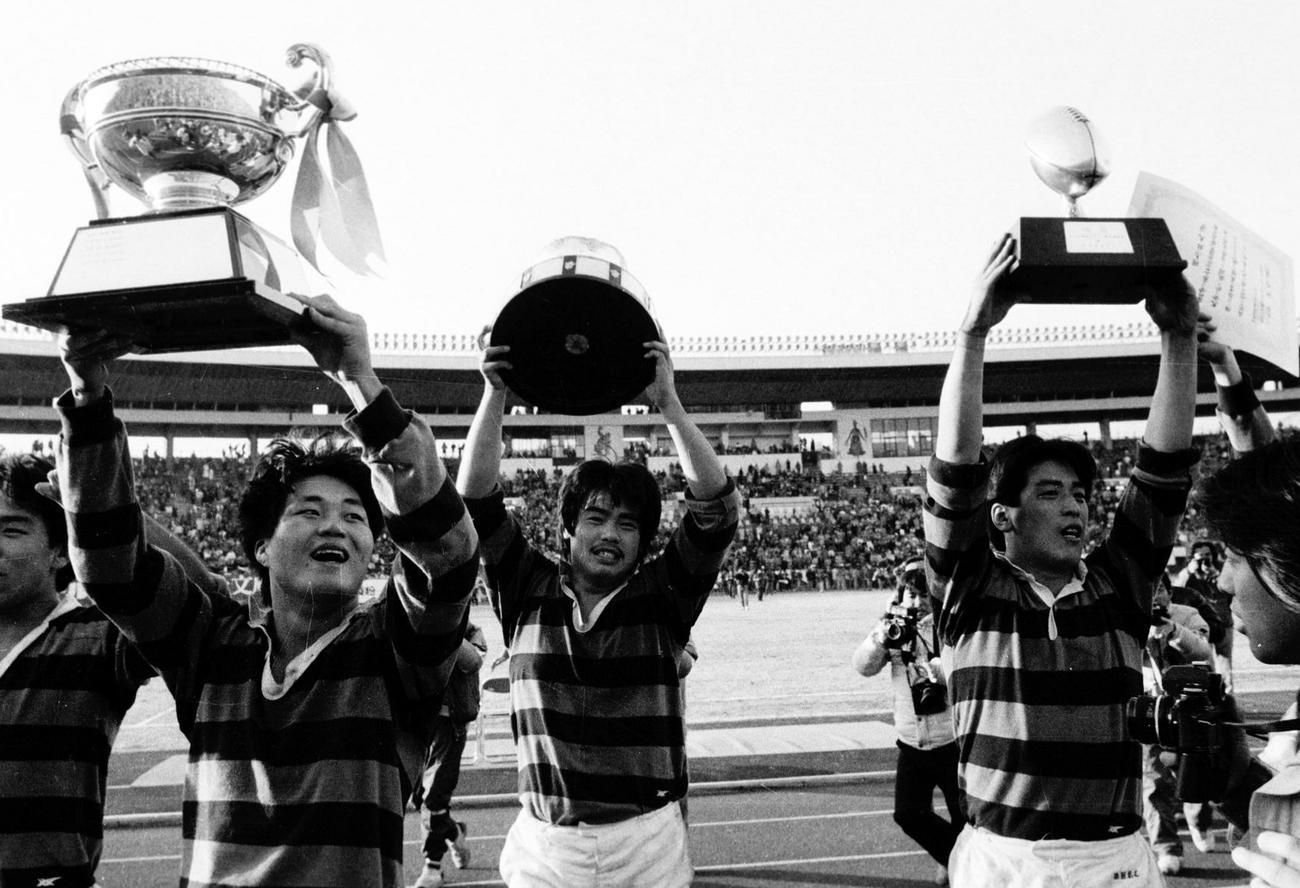 85年1月、大学選手権で優勝しカップを掲げる(左2人目から)同大・円井良、武藤規夫、土田雅人
