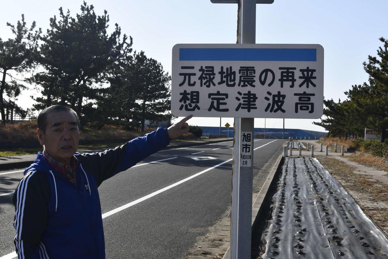「元禄地震の再来想定津波高」と書かれた看板示す戸井さん(撮影・平山連)