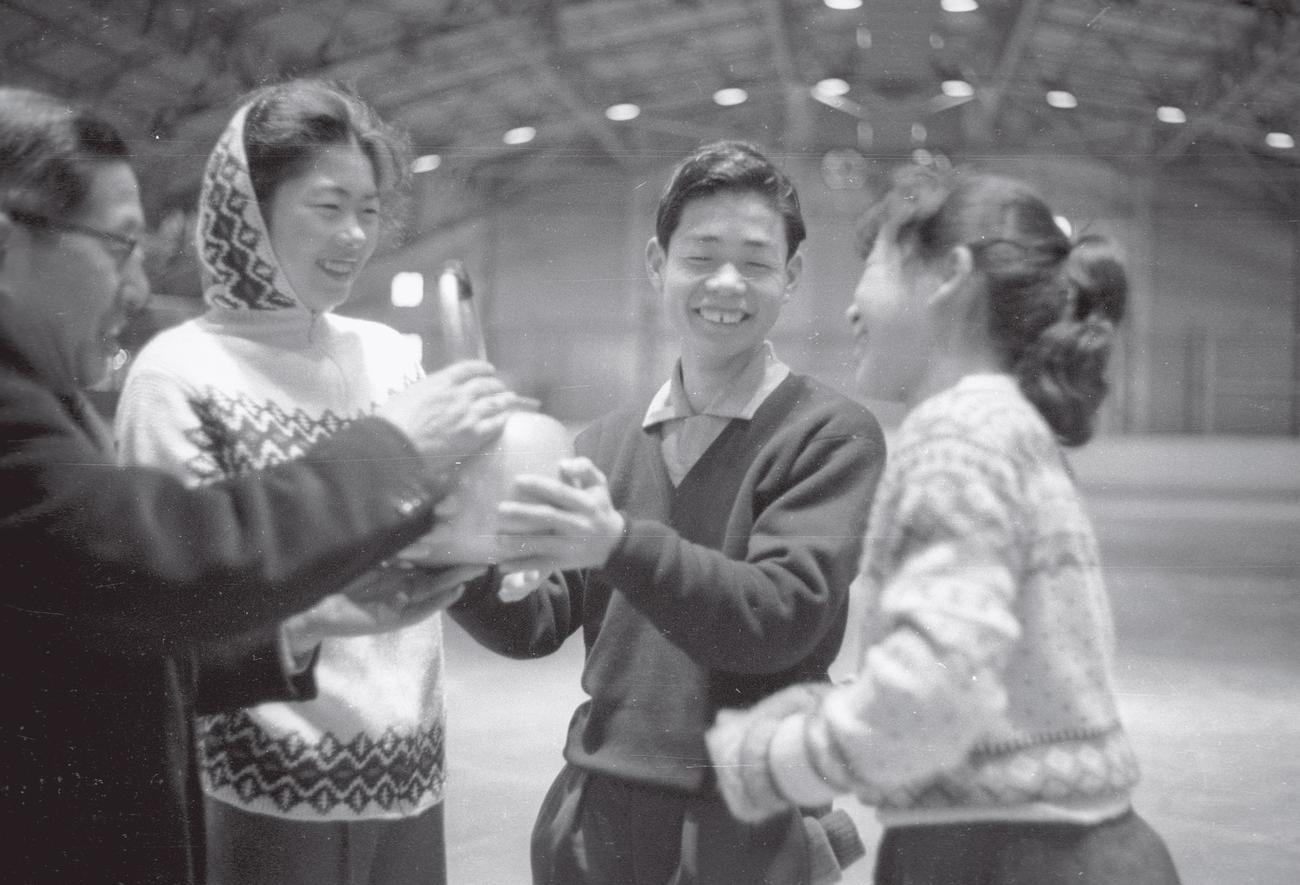 59年12月、スコーバレー冬季五輪代表合宿の早朝練習で、やかんのお湯で暖を取る代表選手たち。左から田山秀士監督、上野純子、佐藤信夫、福原美和