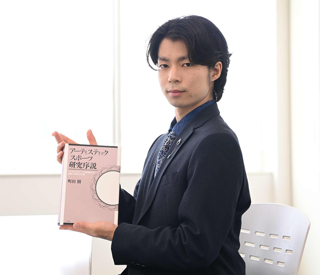 著書「アーティスティックスポーツ研究序説」を手に写真に納まる町田樹氏(撮影・鈴木みどり)