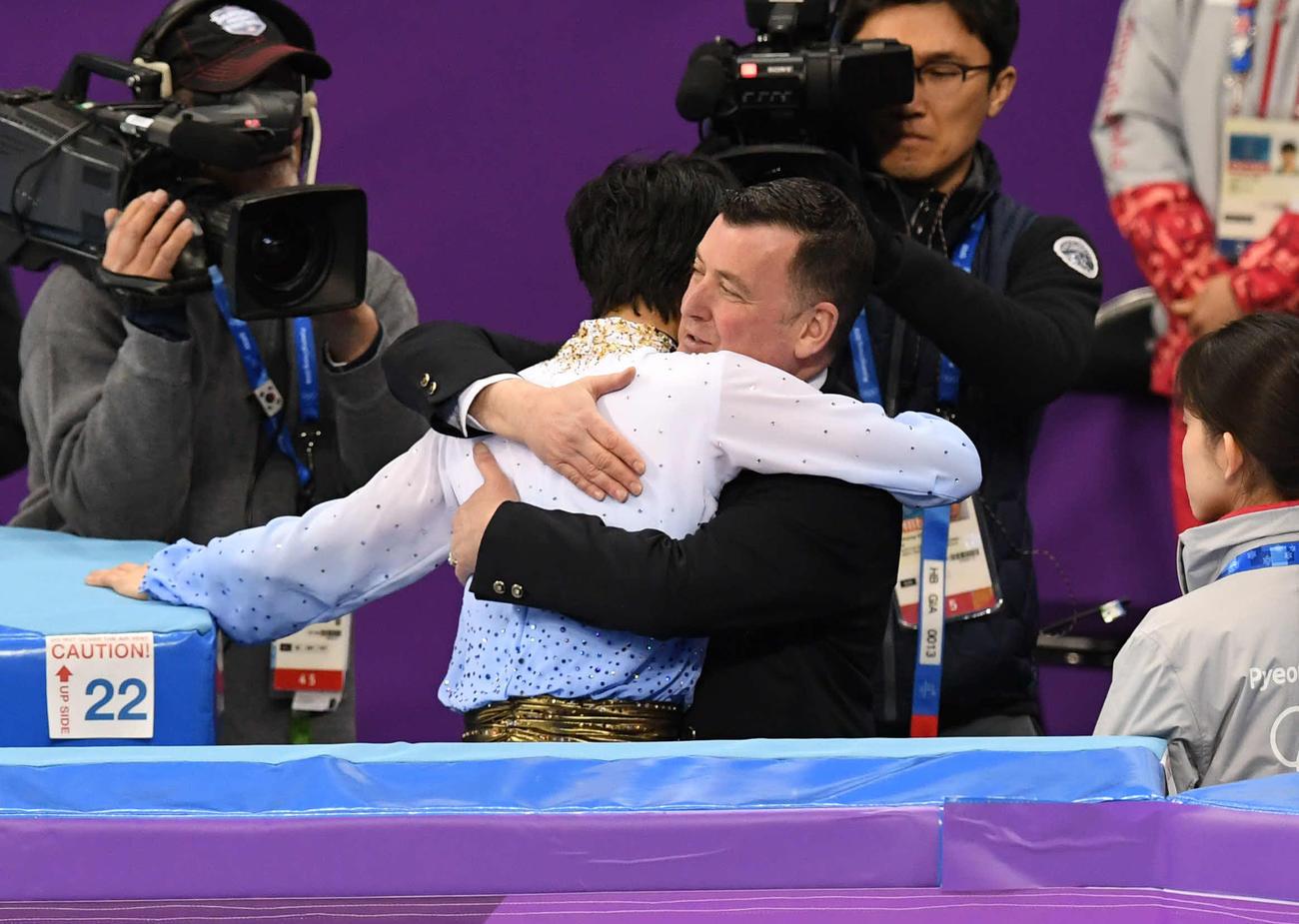 ブライアン・オーサー・コーチと抱き合う羽生結弦(中央左)(2018年2月16日撮影)