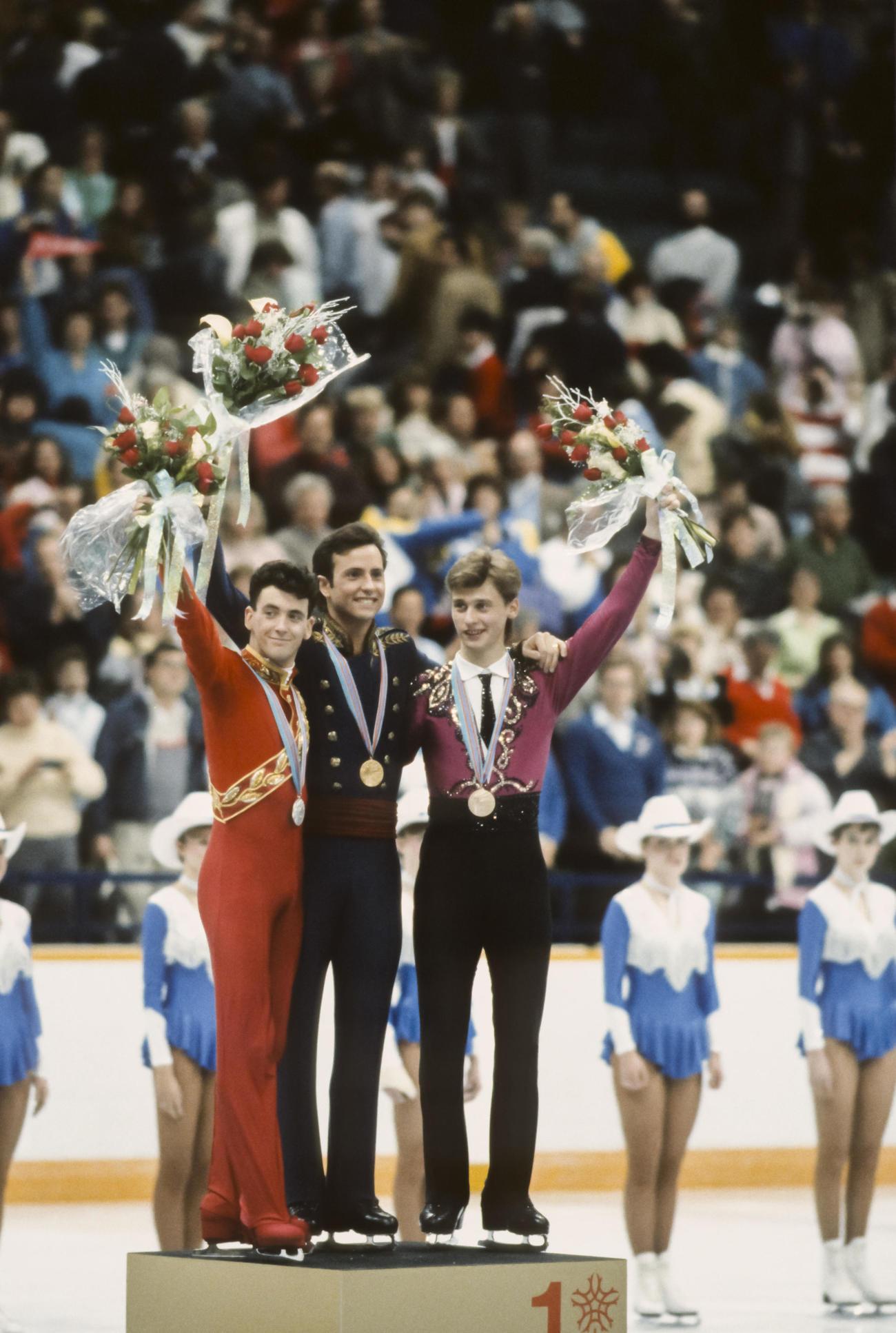 88年2月、「ブライアン対決」となったカルガリー五輪フィギュアスケート男子シングルで優勝したブライアン・ボイタノ(中央)と銀メダルのブライアン・オーサー(左)は表彰台で声援に応える。右は銅メダルのヴィクトール・ペトレンコ(ゲッティ=共同)