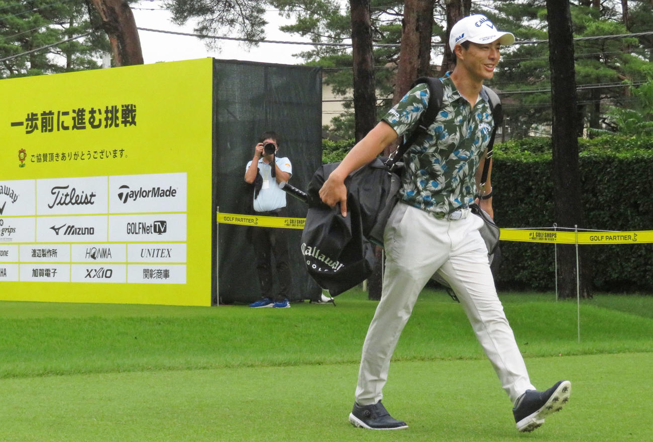 ゴルフパートナー・エキシビション 第1日 1番、ティーショットを放った後、セルフプレーのためバッグを担ぎながら笑顔を見せる石川遼(2020年7月9日撮影)