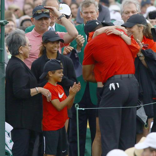 最終ラウンド、逆転で優勝を果たし、家族と喜ぶタイガー・ウッズ(右手前)(共同)