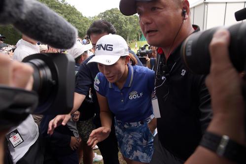 ホールアウト後、多くの報道陣やギャラリーに囲まれながらグリーンを後にする渋野(撮影・佐藤翔太)