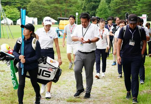 練習場を後にする渋野日向子(左から2人目)を大勢の報道陣が追いかけた(撮影・加藤諒)