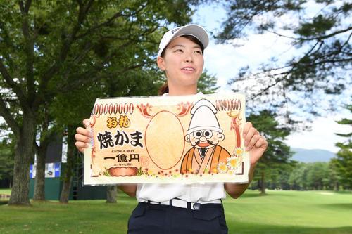 報道陣から1億円のお札状のお菓子を受け取り、笑顔を見せる渋野(撮影・加藤諒)
