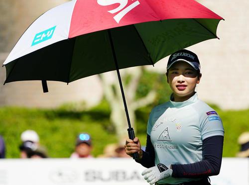 1番、ティーショットを放ち、傘を差してコースに出る小祝(撮影・加藤諒)