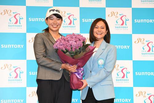 サントリー所属となった渋野(左)は宮里アンバサダーから青いバラの花束をプレゼントされて笑顔を見せる(撮影・山崎安昭)