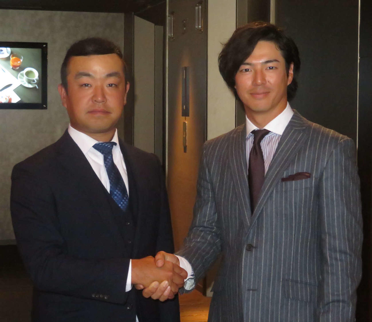 選手会の会長に就任し、前会長の石川(右)と握手を交わす時松