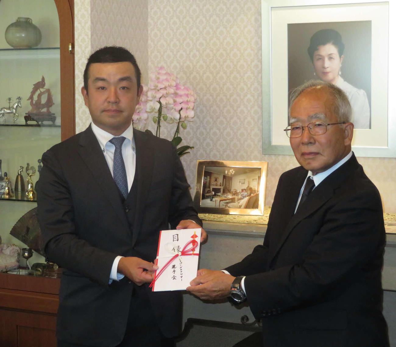 選手会の時松隆光会長(左)は、高松宮妃癌研究基金の関谷剛男理事長に目録を手渡した
