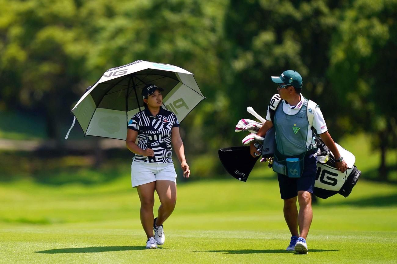 5番、鈴木は傘をさしながらフェアウエイを歩く。右は清水キャディー(Getty Images/JLPGA提供)