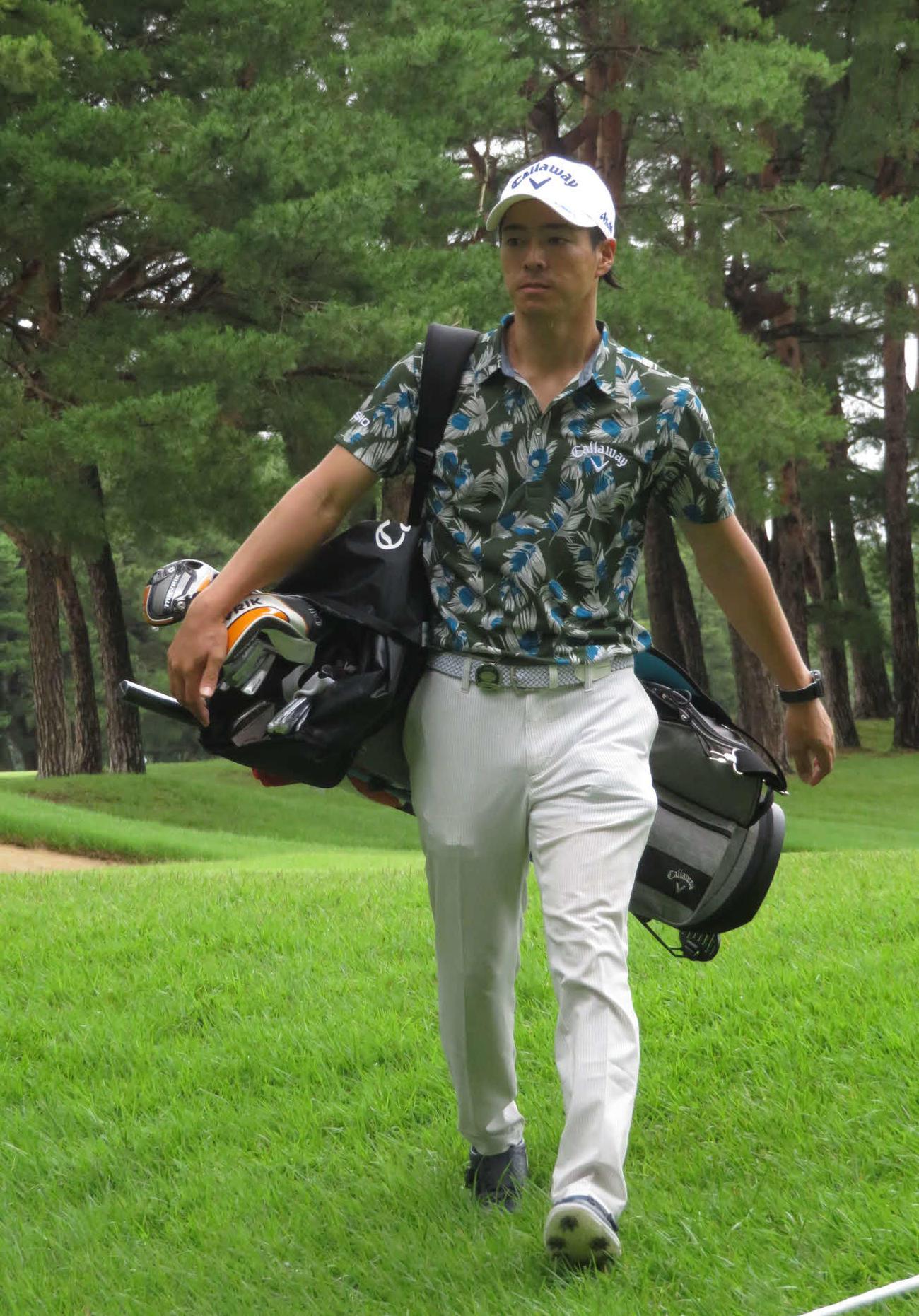 セルフプレーのためバッグを担ぎながら、9番グリーンから移動する石川遼(撮影・高田文太)