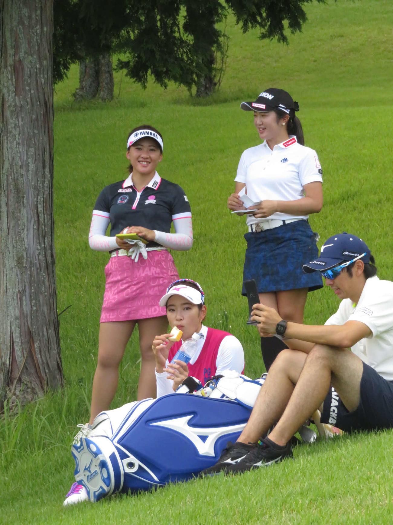 4番、直前にラウンドする組が終わるまで小休憩で栄養補給する原英莉花(手前左)。永井花奈(後方左)と林菜乃子(同右)は談笑