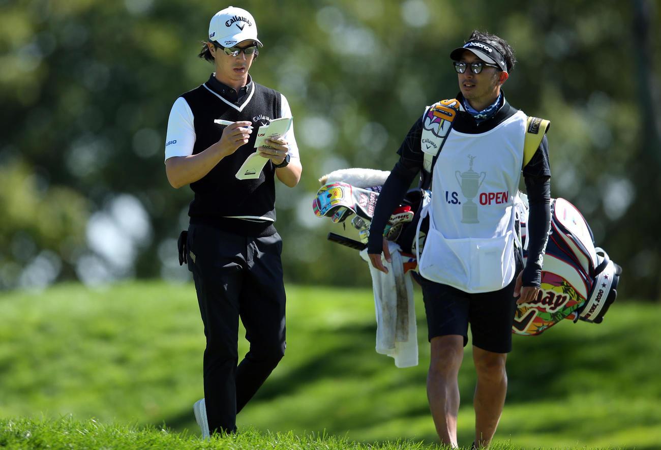 全米オープン選手権最終日 6番、メモを取りながらキャディーと会話する石川遼(ロイター)