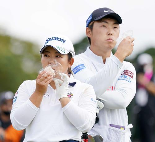 8番前、おにぎりをほおばる浅井咲希(左)と木村キャディー(撮影・江口和貴)