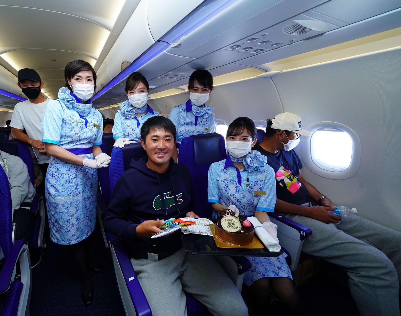 ダンロップ・フェニックスでプロ初優勝を果たし、帰りのチャーター便機内で客室乗務員に祝福された金谷拓実(中央)