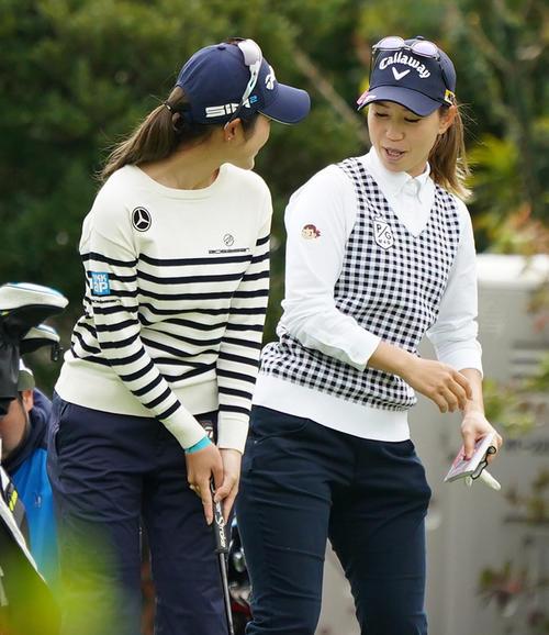 第34回ダイキンオーキッドレディスゴルフトーナメント 練習グリーンで大西葵(左)にヒップアタックであいさつする上田桃子(撮影・清水貴仁)