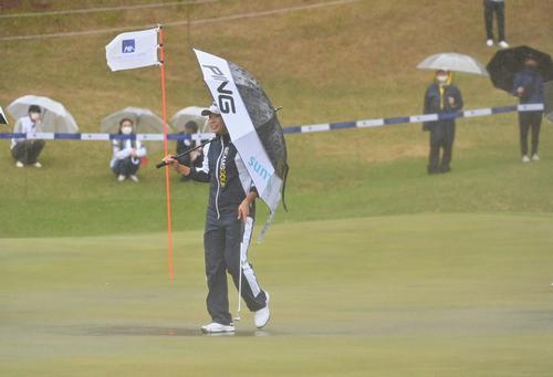 18番、大雨のために試合が中断し、水溜まりのできたグリーンを引き揚げる渋野日向子(撮影・上田博志)
