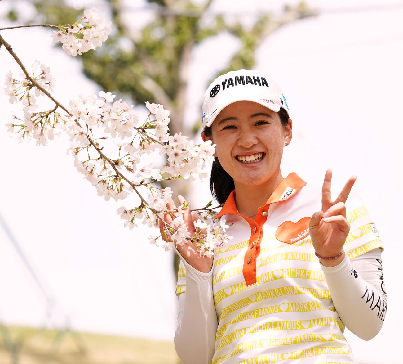 満開の桜の横でピースサインを見せ笑顔の永井(撮影・江口和貴)