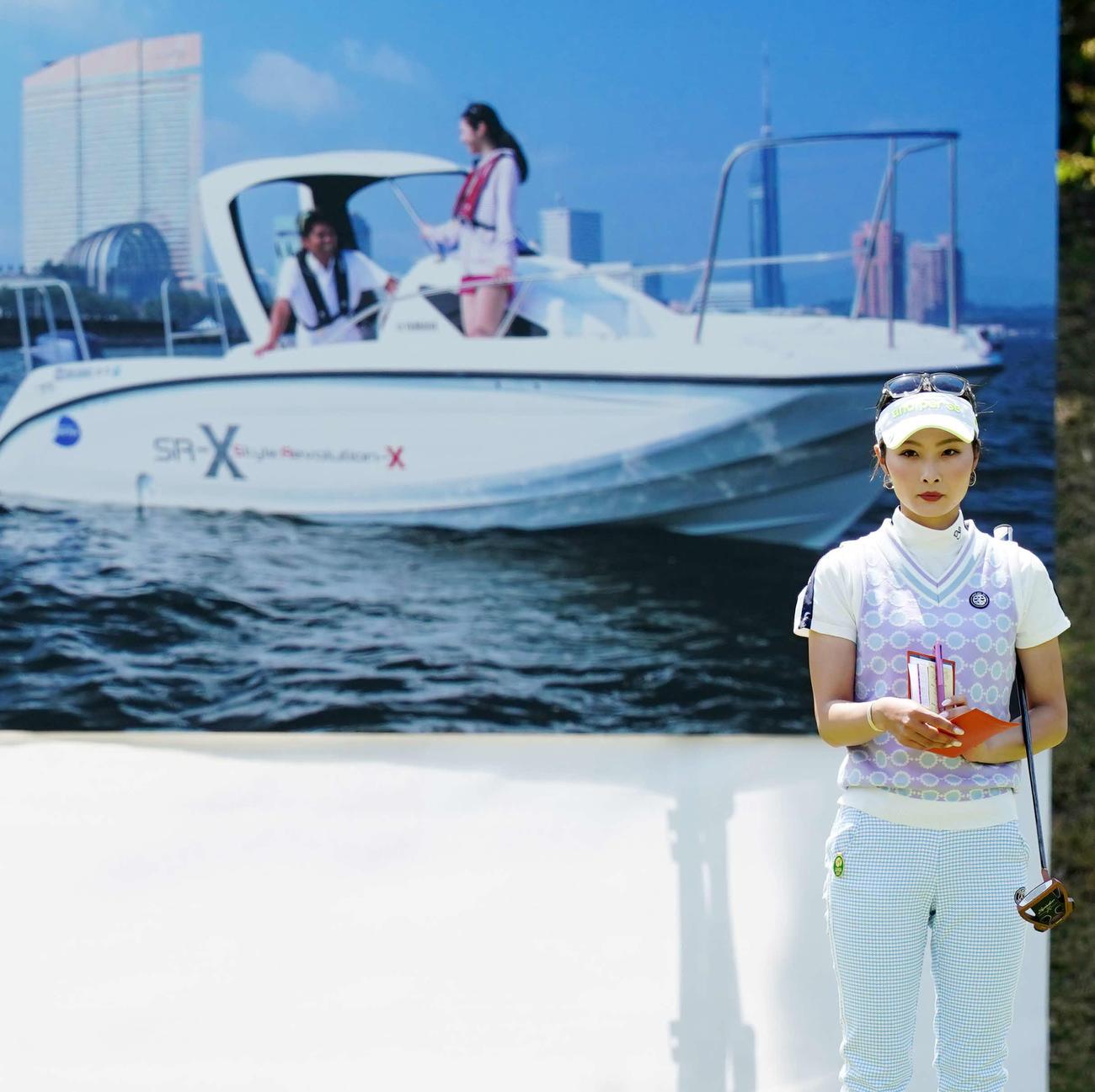 18番、優勝副賞のクルーザーボートの写真ボードを背にプレーする鶴岡(撮影・江口和貴)