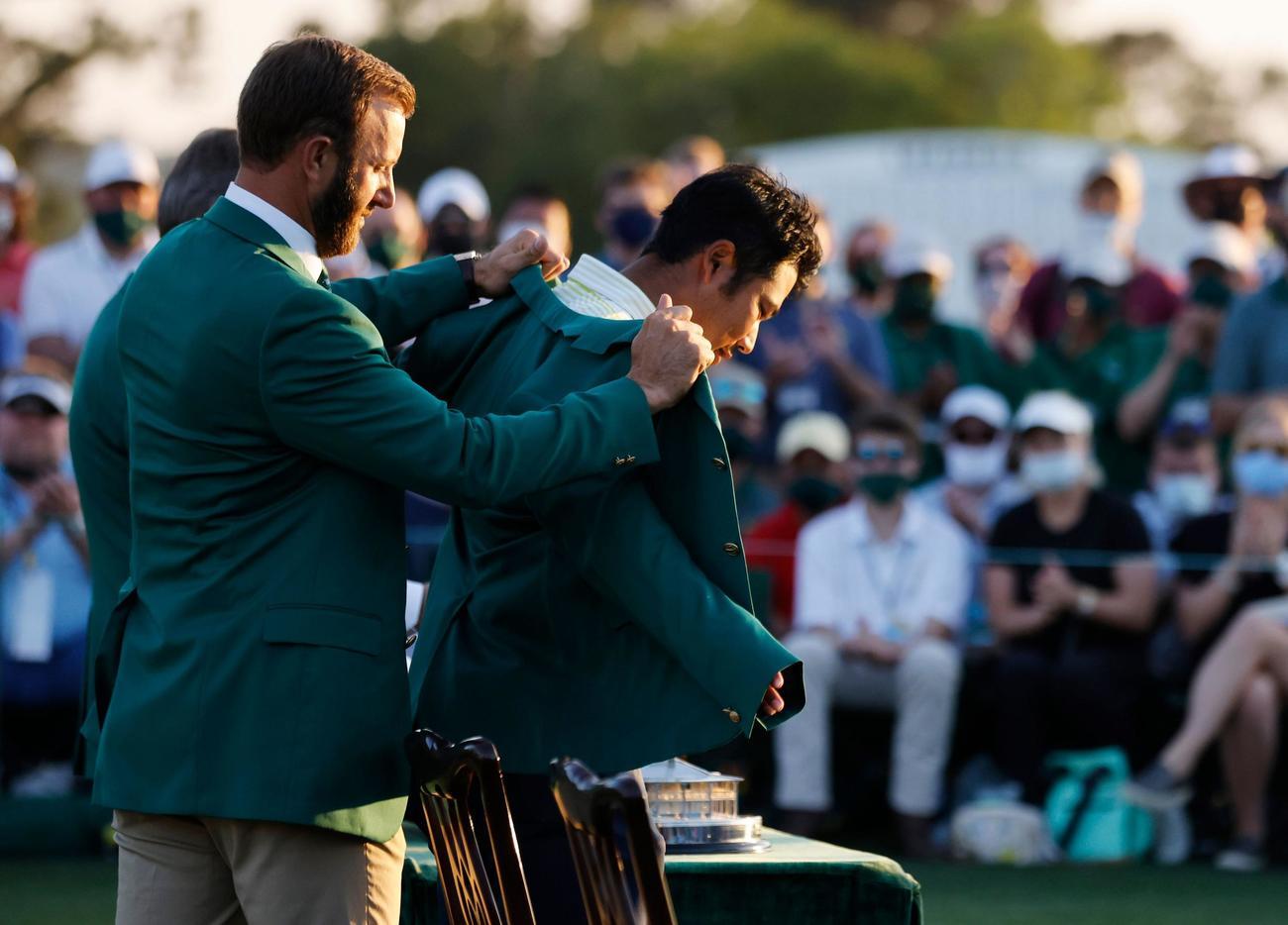 前回優勝のダスティン・ジョンソンからグリーンジャケットを着せてもらう松山(ロイター)