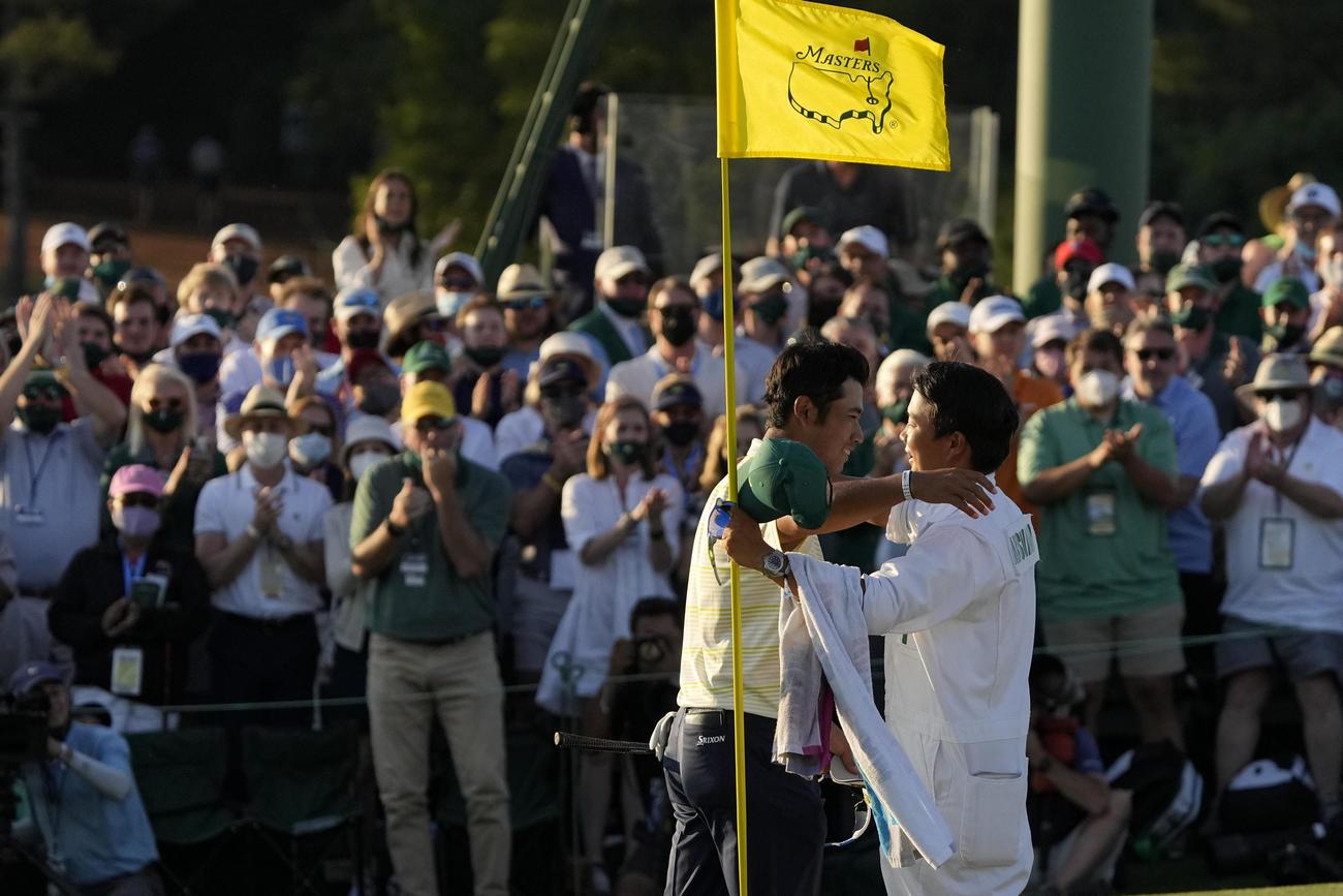 米ゴルフのマスターズ・トーナメントで、日本男子初のメジャー制覇を果たし、キャディー(手前右)と抱き合う松山英樹(AP)