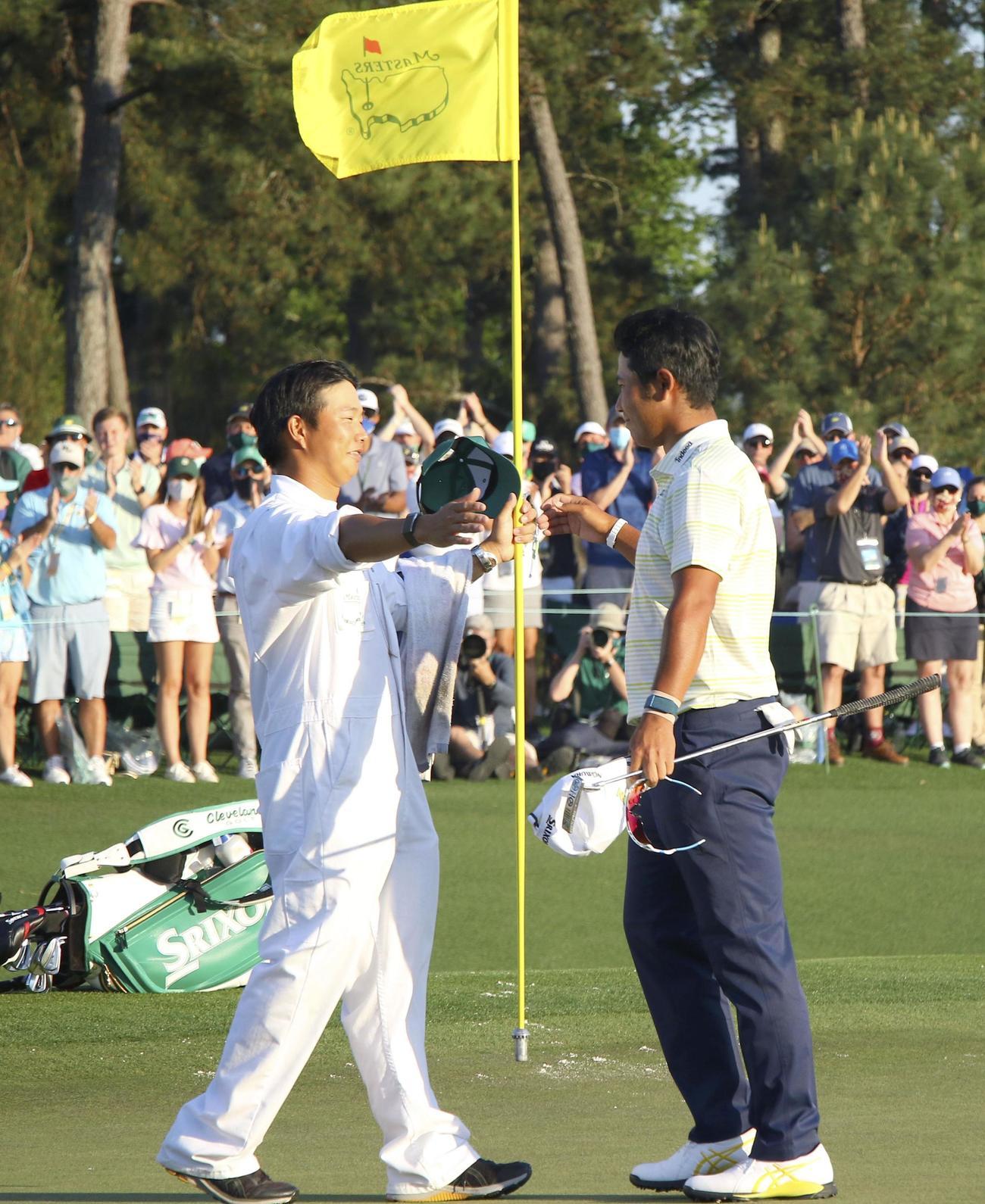 米ゴルフのマスターズ・トーナメントで、日本男子初のメジャー制覇を果たし、キャディー(左)と喜ぶ松山英樹(共同)
