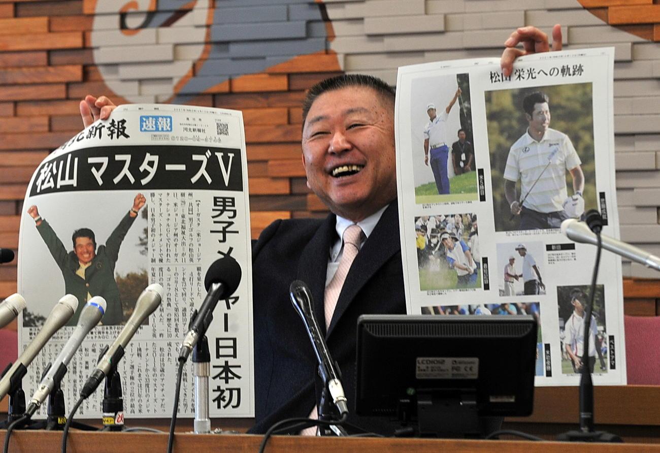 東北福祉大ゴルフ部の阿部監督は会見で松山のメジャー制覇を報じる地元紙の号外を掲げて笑顔を見せる